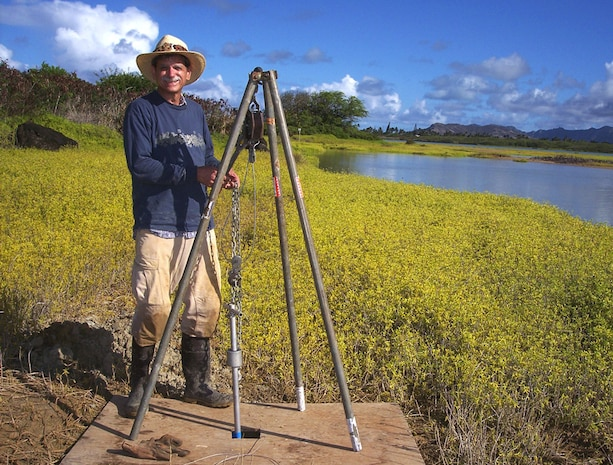 Archaeologist coring in Nuupia Fishponds to extract sediment samples.  These samples provide evidence of pond formation and pollen from the different plants that once lived along the ponds.  The sediment from the core indicates that the fishpond was likely constructed by ancient Hawaiians about 700 years ago.