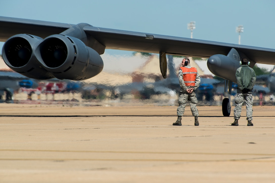 U.S. Air Force Senior Airman Lucas Guthrie and Airman 1st Class Jacob Ranum, 2nd Aircraft Maintenance Squadron crew chiefs, prepare to marshal a B-52H Stratofortress prior to a sortie, April 19, 2013, Barksdale Air Force Base, La. The aircraft is participating in a nuclear exercise at Minot AFB, N.D., and is piloted by aircrew assigned to the 343rd Bomb Squadron at Barksdale. (U.S. Air Force photo by Master Sgt. Greg Steele/Released)