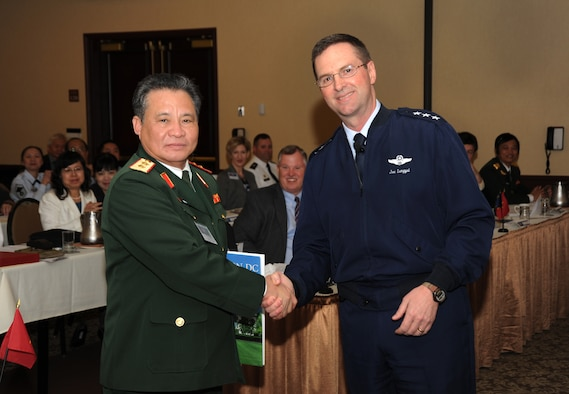 U.S. Air Force Lt. Gen. Joseph L. Lengyel (right), Vice Chief, National Guard Bureau, gives a book as a gift to Lt. Gen. Tran Quang Khue (left), Deputy Chief of General Staff of the Vietnam People's Army, following Lengyel's speech at the State Partnership Program Workshop held in Portland, Ore., April 19. Khue led a Vietnam delegation which visited Oregon National Guard facilities as part of the ongoing partnership between the Oregon National Guard and Vietnam, made official in November 2012. The National Guard Bureau program pairs emerging democracies with National Guard states. (Air National Guard photo by Air Force Tech. Sgt. John Hughel, 142nd Fighter Wing Public Affairs)