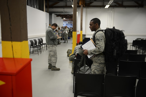 SPANGDAHLEM AIR BASE, Germany – U.S. Air Force Airman 1st Class Daniel Taylor carries his belongings before processing the Personnel Deployment Function line here April 4, 2013. This is Taylor's first deployment since he joined the Air Force. (U.S. Air Force photo by Staff Sgt. Nathanael Callon/Released)