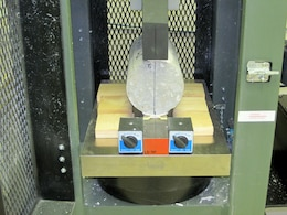 A test core from two lifts of self-consolidating concrete undergoes a splitting tension test, with the location of the joint indicated by the line across the diameter. The average peak force registered was 40,000 lbs and the joint strength was in the range of 550 to 600 psi. Splitting tension testing and direct shear testing provided the information the Olmsted team needed to adopt the warm joint. (U.S. Army Corps of Engineers photo by Dave Kiefer)