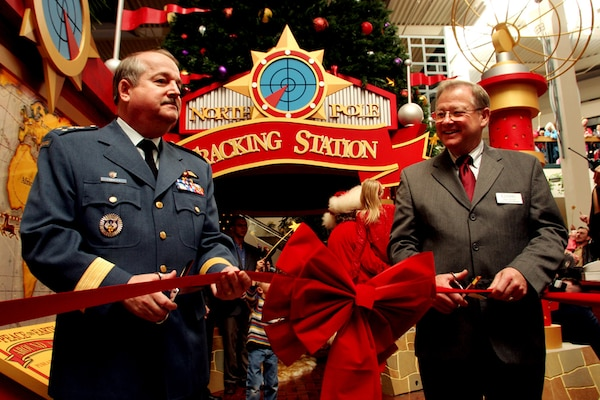 Lt.-Gen. Rick Findley, deputy commander of the North American Aerospace Defense Command, and Robert Taylor, senior property manager at Citadel Mall, perform the ceremonial ribbon cutting during the Nov. 18 launch of the Citadel Mall's Santa Tracking Station. Photo by Tom Kimmell