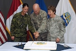 Gen. Gene Renuart, commander of the North American Aerospace Defense Command and U.S. Northern Command, cuts NORAD's birthday cake with Canadian Forces Cpl. Julie Lehoux (left) and Chief Warrant Officer 4 Mary Koepp. Canada and the United States signed the NORAD Agreement May 12, 1958 Photo by Petty Officer 1st Class Joaquin Juatai