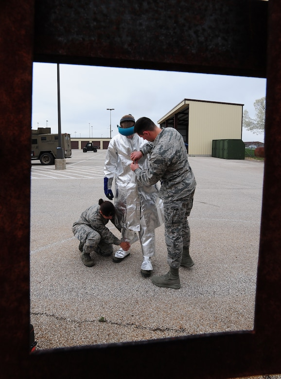 Airmen 1st Class Stephanie Burjass and Joseph Dolan, 509th Security Forces Squadron response force members, help Airman 1st Class Isaac Fox, 509th Security Forces Squadron response force member, don protective equipment before he performs a breeching exercise at Whiteman Air Force Base, Mo., April 16, 2013. Breeching exercises prepare Airmen for situations that require them to break into a locked room or building. (U.S. Air Force photo by Staff Sgt. Nick Wilson/Released)
