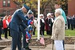 Rome community members stand while Lt. Col. Wendy Rickards, Northeast Air Defense Sector Canadian Component commander, and Warrant Officer Norm Macoomb, NEADS Canadian Component unit warrant officer, place a wreath next to the Northeast Air Defense Sector's wreath during a joint, bi-national Veterans Day ceremony in Rome, N.Y.