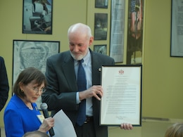 At the Marine Corps Association's 100th anniversary celebration, Virginia State Sen. Toddy Puller, daughter in law of Gen. Chesty Puller, presents a resolution passed by the Virginia General Assembly recognizing the MCA as retired Maj. Gen. Ed Usher, MCA President and CEO, looks on. The celebration was April 25, 2013, at the National Museum of the Marine Corps.