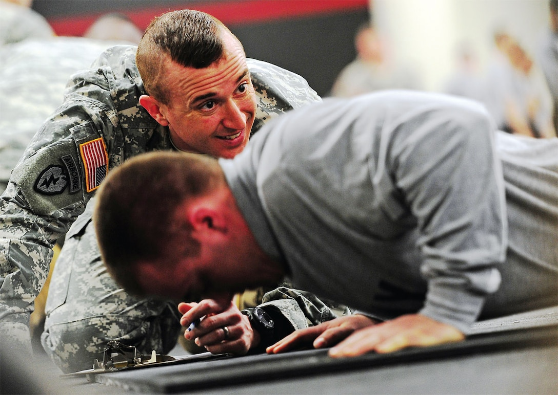 Parachute infantryman Spc. Sean Tighe, assigned to B Company, 1st Battalion (Airborne), 501st Infantry Regiment, a native of South Yarmouth, Mass., performs push-ups as 1st Sgt. Landon Sahagun, B/1-501st Inf., a native of Jasper, Ala.,  counts his repetitions during the Expert Infantryman Badge testing on JBER, Monday. Command Sgt. Maj. Bernie Knight, U.S. Army Alaska command sergeant major, wrote physical training is both a unit and an individual responsibility. (U.S. Air Force photo/Justin Connaher)