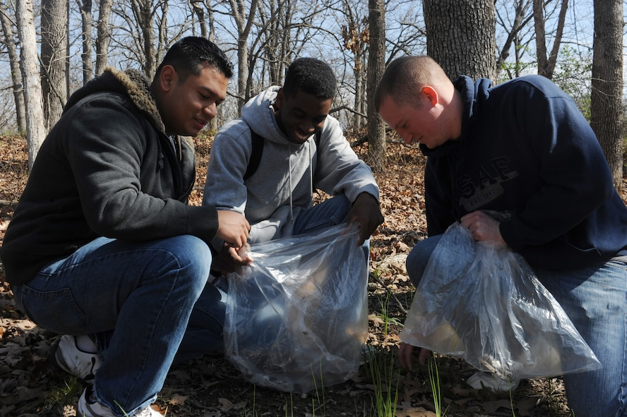 Airman 1st Class Manuel Gurrion (left), and Airman 1st Class Devyn Ransom and Senior Airman James Davis, 509th Maintenance Squadron aerospace ground equipment maintainers, pick up trash during a trash collection at Knob Noster State Park, Mo., April 20, 2013. Members of Team Whiteman were joined by spouses and dependents in carrying out the mass cleanup. (U.S. Air Force photo by Airman 1st Class Bryan Crane/Released)