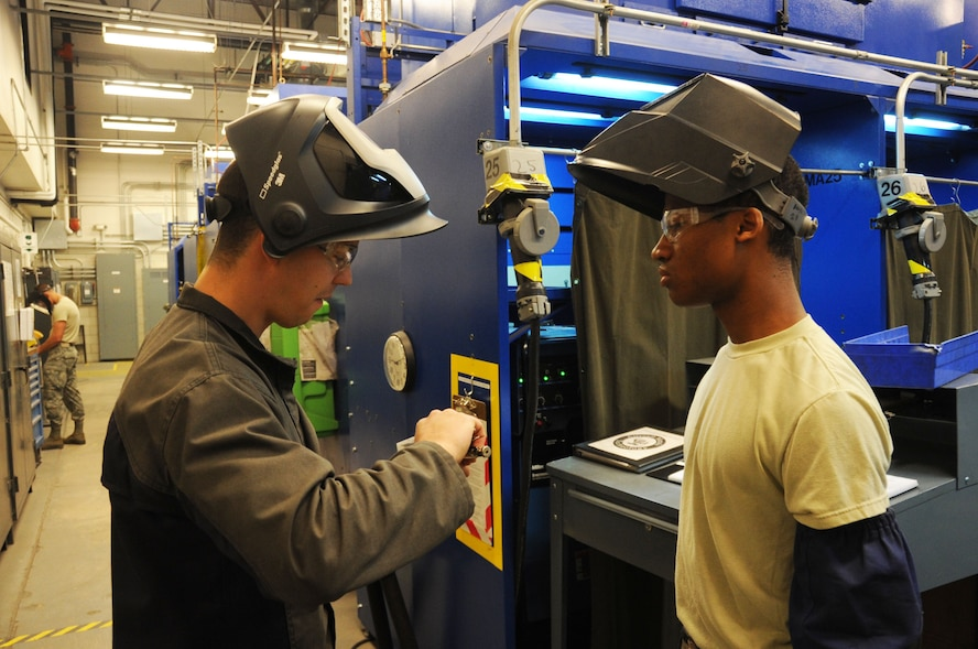 Air Force Staff Sgt. Jordan Loving (left), 361st Training Squadron aircraft metals technology instructor, reviews a tungston inert gas weld exercise with Airman 1st Class Michael Abney (right), 361st TRS Airman-in-Training, at Sheppard Air Force Base, Texas, April 25, 2013.  Loving was named the 2012 AETC Airman Instructor of the Year.  (U.S. Air Force photo by Dan Hawkins/Released)