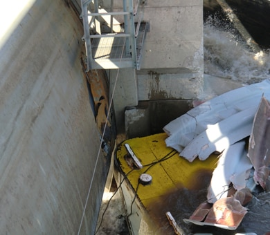 This photo shows damage to a concrete pier and the Tainter gate. Photo left, a 15-foot hole in the upstream portion of the Tainter gate; photo top, concrete damage to the upstream pier; photo right, barge cargo covers that were damaged after alliding with Marseilles Dam.