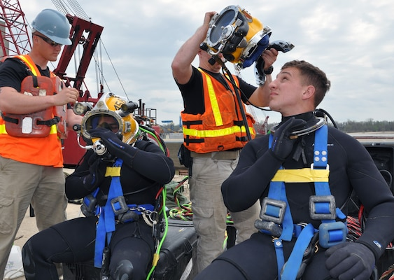 (Seated right) Spc. Jacob Feyers, 19, from Detroit, Mich., and a veteran of Hurricane Sandy recovery diving, peers into his superlight 37 Kirby Morgan helmet as he is assisted in suiting up for his descent into the Olmsted lock culvert.