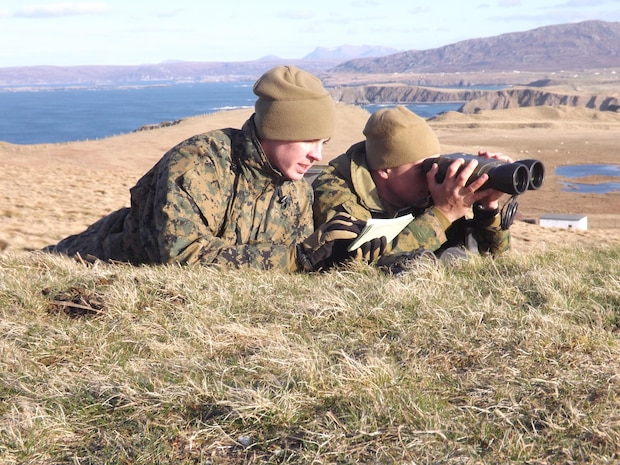 """Lance Cpl. Antonio Ramirez assists Lance Cpl. Keith Bohannon, in calling in precision naval gunfire during Exercise Joint Warrior 13.1 in Cape Wrath, Scotland, April 19.   Joint Warrior 13.1 or JW 13.1, is an enduring NATO exercise supported by the ANGLICO community to facilitate joint collective training and pre-deployment training for UK, NATO and Allied units and their staffs in preparation for employment as part of a Combined Joint Task Force. The exercise featured 60 separate naval units, operating at points around the coast of Scotland, April 15-25.  """"Joint Warrior is conducted in the spring and autumn of each year and provides training for all three UK armed services as well as visiting units from allied nations,"""" said James Krajicek, U.S. Marine Corps Forces Europe, planning and assessments officer. """"The seas and skies around Orkney played host to elements of the largest tactically focused military exercise in Europe.""""   Countries taking part in the maritime part of the exercise included the United Kingdom, Belgium, Germany, Holland, France, Norway, Denmark, Canada and Sweden.  Ramirez and Bohannon are both forward observers with 2nd ANGLICO Co., 2nd Marine Division, out of Camp Lejeune, N.C."""