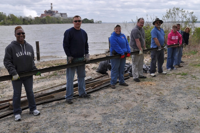 Volunteers carry a heavy piece of metal off the Potomac River beach April 22 during Marine Corps Systems Command's third annual Earth Day and Shoreline Cleanup event. MCSC's Safety Office orchestrated the event held at Hospital Point, Quantico, Va