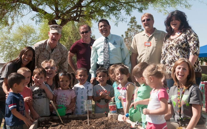 Colonel Robert Kuckuk, Marine Corps Air Station Yuma commanding officer, and station personnel from both the Environmental Department and the Child Development Center take a break from helping children plant flower and vegetable seeds at the CDC April 25. The final event brought a close to the week-long Earth Day celebration to raise awareness about being environmentally conscious caretakers of the land that we live, train and operate on as a community here at MCAS Yuma.