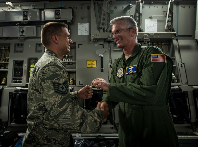 Gen. Paul Selva, Air Mobility Command commander, hands the keys to a new C-17 Globemaster III to Tech. Sgt. Gary Pongetti, 437th Aircraft Maintenance Squadron crew chief April 25, 2013, at Joint Base Charleston – Air Base, S.C. Joint Base Charleston is scheduled to receive two additional C-17s this year, as Boeing completes work on the Air Force's final Globemasters. The first C-17 to enter the Air Force's inventory arrived at Charleston Air Force Base in June 1993. The C-17 is capable of rapid strategic delivery of troops and all types of cargo to main operating bases or directly to forward bases in the deployment area. (U.S. Air Force photo/ Senior Airman Dennis Sloan)