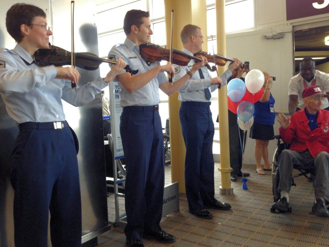 Members of the Air Force Strings greet Honor Flight members at National Airport