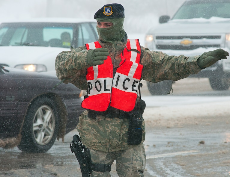 Staff Sgt. Melissa Norton, 90th Security Forces Squadron, directs traffic at the intersection of Shreiver Road and Randall Avenue April 16 on F. E. Warren Air Force Base, Wyo. A spring snow storm hit the Cheyenne area knocking out power to part of the base including the traffic light at the intersection. (U.S. Air Force photo by R.J. Oriez)