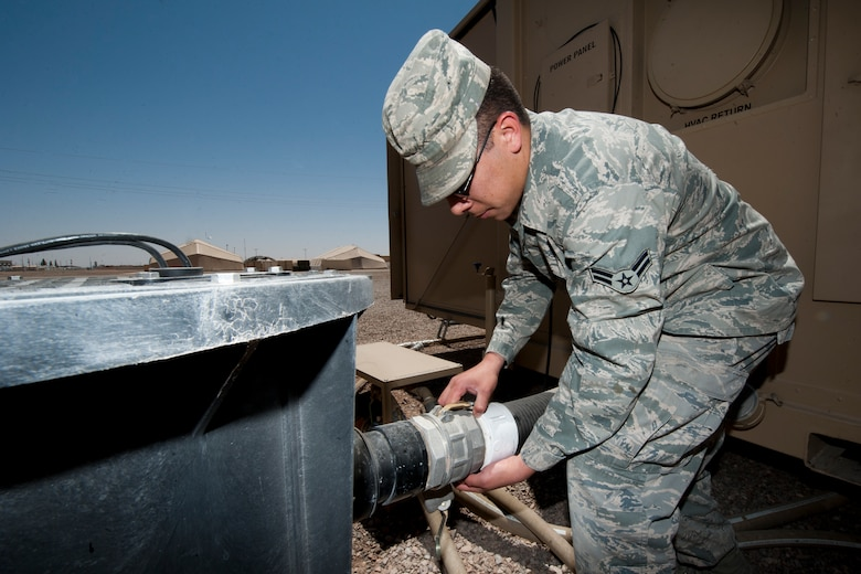 Airman 1st Class Trevor Dickerson, 49th Materiel Maintenance Squadron water and fuels system maintainer, removes a pump from a macerator used for the new hygiene system at Holloman Air Force Base, N.M., April 24. The 49th MMS was the first unit to receive and test the new hygiene system, complete with latrines and showers, which will eventually be utilized in forward deployed locations. (U.S. Air Force photo by Airman 1st Class Daniel E. Liddicoet)