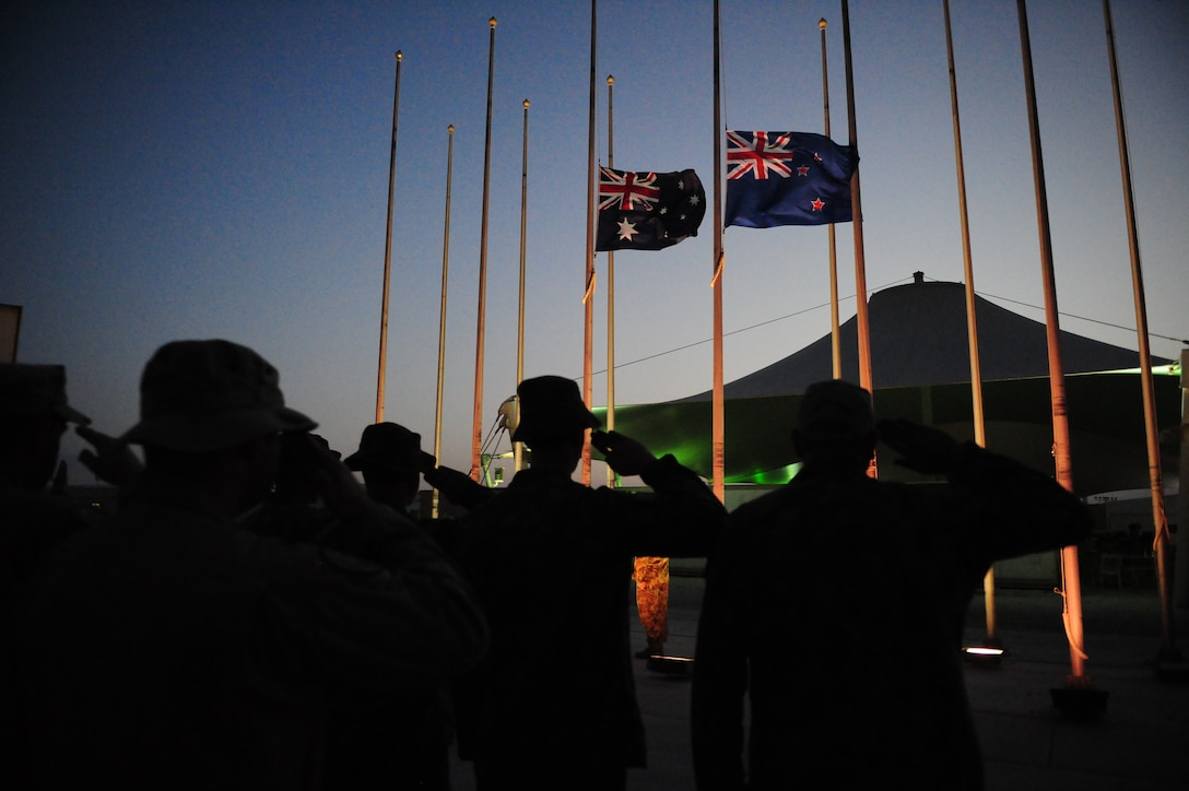 """SOUTHWEST ASIA – The Royal Australian Air Force invited the Grand Slam Wing to take part in a dawn, wreath-laying service April 25 to remember all who served and died in all wars, conflicts and peacekeeping operations in which Australian and New Zealand defense forces have been engaged. The dawn service focuses on the quiet moments before dawn during conflict, where soldiers were woken up to """"stand-to"""" in the quiet moments before another day of battle would begin. The Thursday morning ceremony here began at 4:20 a.m. – the time ANZAC Forces made landfall on Gallipoli in 1915 -- hosted by RAAF Task Unit 633.2.5 Wing Commander Paul Gibbs, followed by a hymn, dedication, sonnet and requiem. Coalition representatives here laid a wreath, including the Australians, New Zealanders, British, Americans, French, Canadians, Italians and Belgians. After the laying of wreaths, an ode of remembrance was read before a playing of the last post. After the moment of silence, reveille played, a prayer given and the ceremony concluded with the national anthems of Australia and New Zealand. (U.S. Air Force photo/Master Sgt. Brendan Kavanaugh)"""