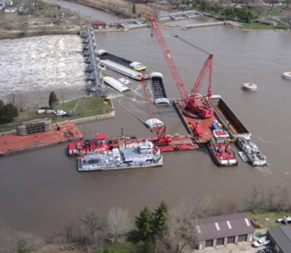 """The Rock Island District's crane, known as the """"HERCULES,"""" unloads cargo from one of the submerged barges near the Marseilles Dam in Marseilles, Ill., April 24, 2013. Salvage operations will continue to remove the remaining barges."""