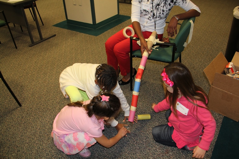 Children of employees at SWD participate in a roller coaster building activity during Take Your Sons and Daughters to Work Day. The young children had to build a roller coaster out of tolilet paper rolls and then drop a marble down it to see if it would work.