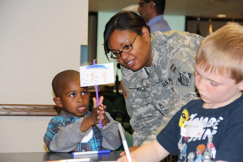 Staff Sgt. Leah Holly, an SWD administrative assistant, admires her 5-year-old sons art project displaying animation during Take Your Sons and Daughter to Work Day.