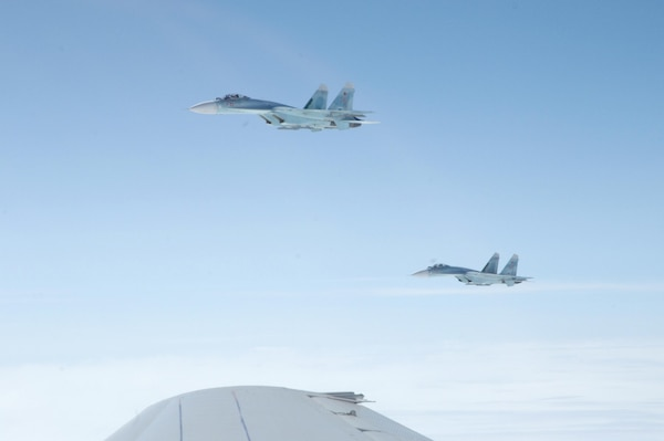 OVER THE PACIFIC OCEAN – A pair of SU-27 fighters escorts a simulated hijacked airliner during the second day of flying for Exercise Vigilant Eagle Aug. 9, 2011. The Russian fighters followed and monitored the aircraft while it was in Russian airspace, handing it over to U.S. F-15 fighters from Elmendorf Air Force Base, Alaska, when it entered U.S. airspace. (U.S. Air Force photo by Tech. Sgt. Thomas J. Doscher)