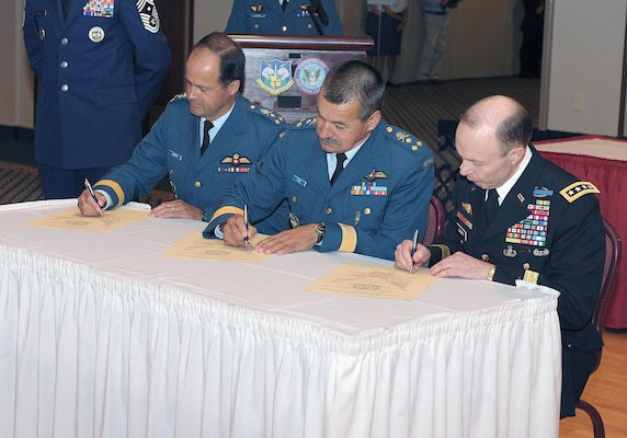 PETERSON AIR FORCE BASE, Colo. - Canadian Forces Lt.-Gen. Tom Lawson, incoming North American Aerospace Defense Command deputy commander, Canadian Forces Lt.-Gen. Marcel Duval, the outgoing deputy commander, and Army Gen. Charles Jacoby, sign the change of office documents during a ceremony on Peterson Air Force Base, Colo., Aug. 15, formally making Lawson the 22nd NORAD deputy commander. Lawson comes to NORAD after previously holding the position of Assistant Chief of the Air Staff for the Canadian Forces.   (U.S. Air Force photo by Tech. Sgt. Aaron Bujan)