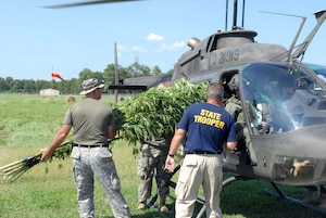Arkansas Guard members help State Police remove marijuana plants from a Guard helicopter during a recent eradication mission in support of the National Guard's Counterdrug Program.