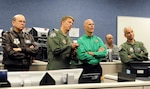 "TYNDALL AIR FORCE BASE, Fla. - Col. Randy Spear (second from left), 601st Air and Space Operations Center commander, points out a simulated ""track of interest"" on a radar screen during an exercise to Florida Gov. Rick Scott at Tyndall Air Force Base, Fla., Jan. 5. Scott came to Tyndall to visit with Florida Air National Guardsmen from the 101st Air and Space Operations Group, which provides the manning for the 601st AOC, and to see firsthand the capabilities and assets Tyndall has to offer. 