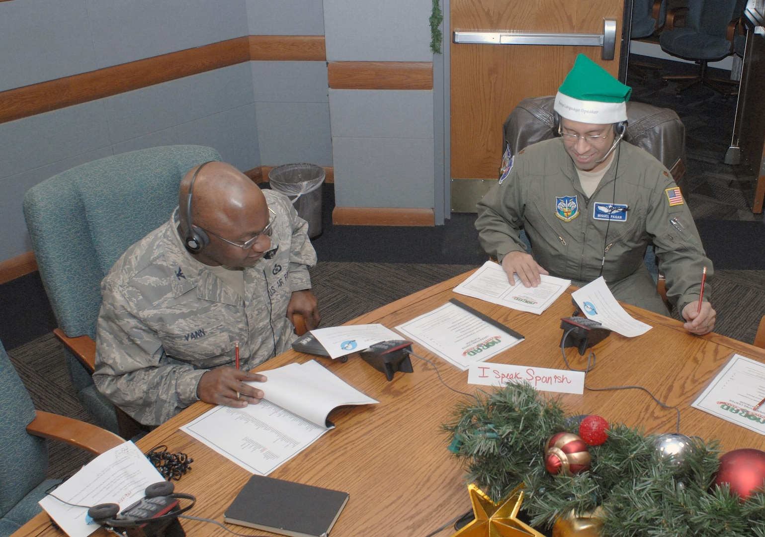 PETERSON AIR FORCE BASE, Colo. - NORAD Tracks Santa volunteers Col. Alvin Vann and Maj. Miguel Pagan answer phone calls from people across the globe looking for Santa. The green hat Pagan is wearing signifies that he speaks a second language and is available to translate should another volunteer receive a call in that language. (U.S. Air Force photo by Tech. Sgt. Thomas J. Doscher)