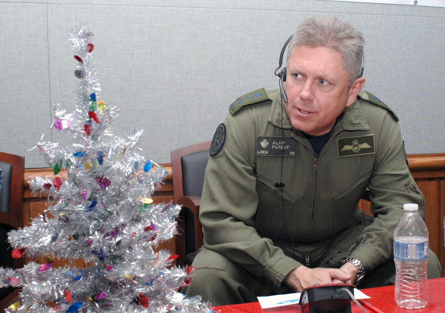 """PETERSON AIR FORCE BASE, Colo. - Canadian Lt.-Gen. Alain Parent, NORAD Deputy Commander, takes some calls at the NORAD Tracks Santa Operations Center Dec. 24, 2012. After this photo was posted on Facebook, a parent commented that their son had just spoken to someone named """"Parent' and that now her six-year-old was """"freaking out."""" (U.S. Air Force photo by Tech. Sgt. Thomas J. Doscher)"""