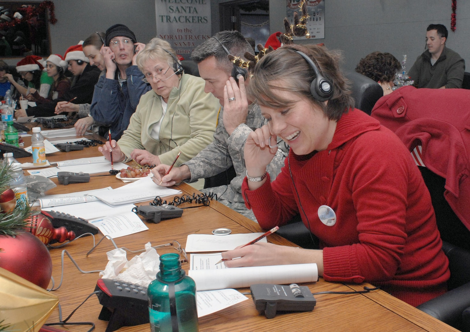 PETERSON AIR FORCE BASE, Colo. - Jennifer Eckels, first time NORAD Tracks Santa volunteer, takes calls at the NORAD Tracks Santa Operations Center. One of the calls Eckels received was from a little boy in Missouri who recently lost his sister. He wanted to know when Santa delivers presents to Heaven. Eckels told him that children in Heaven get their presents first. (US. Air Force photo by Tech. Sgt. Thomas J. Doscher)