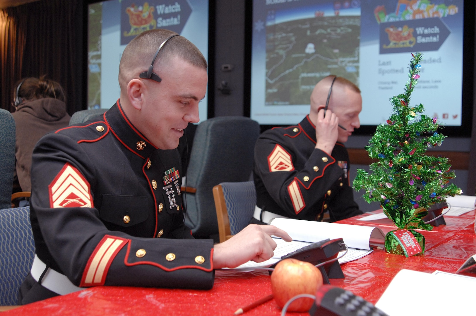 PETERSON AIR FORCE BASE, Colo. - Marine Staff Sgts. Hugh Wood and Randall Ayers, NORAD and USNORTHCOM, take calls at the NORAD Tracks Santa Operations Center Dec. 24, 2012. Wood and Ayers came to the operations center to collect toys for the Marine Corps' Toys for Tots program and took a break to participate in NORAD Tracks Santa. (U.S. Air Force photo by Tech. Sgt. Thomas J. Doscher)