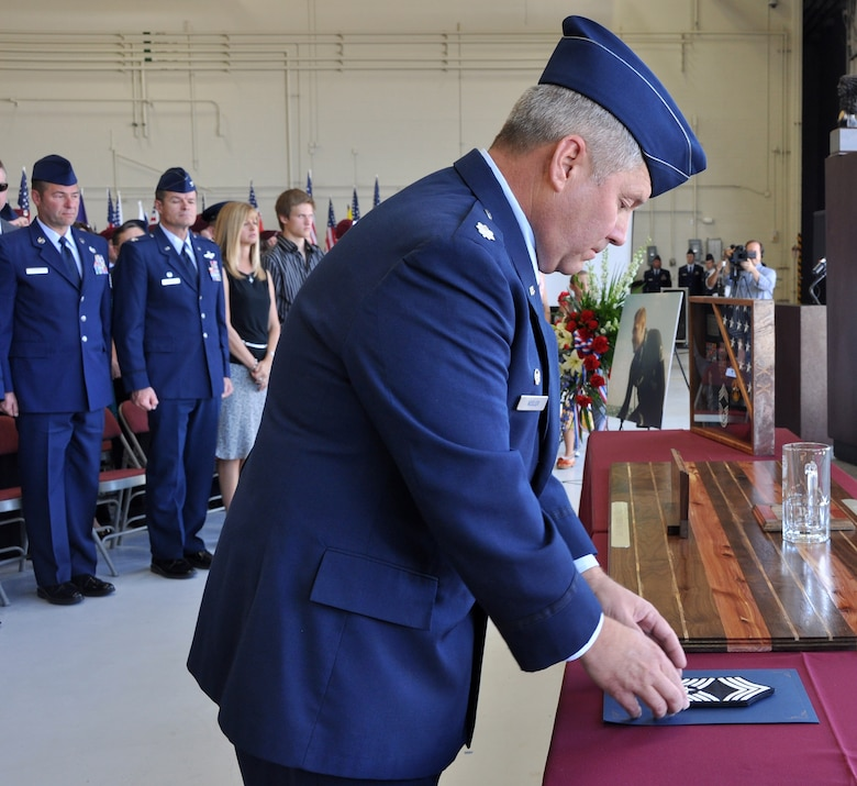 Lt. Col. John Keeler, 306th Rescue Squadron commander, places chief master sergeant stripes on a table during the memorial ceremony of Chief Master Sgt. Nicholas McCaskill, April 27, 2013. McCaskill was killed in Afghanistan April 6, 2013 while he was performing his civilian job as a security contractor. He was promoted to chief master sergeant on Feb. 1, 2013 and was going to have his formal chief pinning ceremony during the May Unit Training Assembly weekend. (U.S. Air Force Photo/ Staff Sgt. Sarah Pullen)
