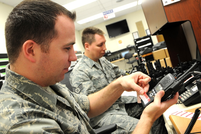 As more than 400 new radios arrived from National Guard Bureau on Apr. 24, Tech. Sgt. Robert Kolenic, foreground, from the 124th Communications Flight (CF), prepares the final encrypting process by loading the encryption keys, adding each radio to the Over the Air Rekeying and placing Communication Security Stickers. Next to Kolenic, Staff Sgt. Mark Holladay, from the 124th CF, attaches clips, antennas and serial numbers to the encrypted radios. (U.S. Air Force photo by Tech. Sgt. Becky Vanshur)