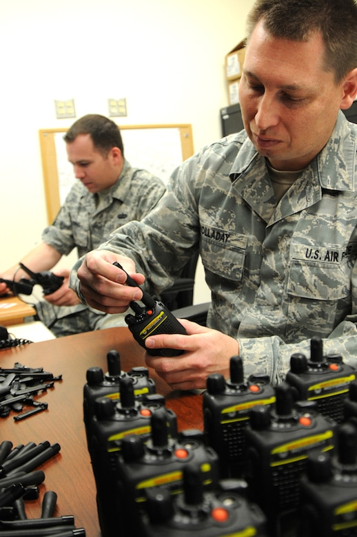 As more than 400 new radios arrived from National Guard Bureau on Apr. 24, Staff Sgt. Mark Holladay, foreground, from the 124th Communications Flight, prepares the encrypted radios by attaching clips, antennas and the serial number system and passes each radio for the final encrypting process performed by Tech. Sgt. Robert Kolenic. (U.S. Air Force photo by Tech. Sgt. Becky Vanshur)