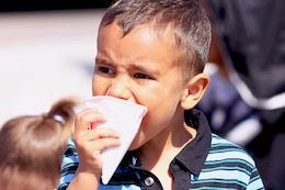 Four-year-old, Tristan bites into a snow cone, as it drips down his face,  during the 18 annual Kids First Fair hosted by Marine and Family Programs at the Paige Fieldhouse here April 27. The event provided live attractions, demonstrations and entertainment including pony rides, face painting and rock climbing.