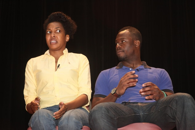 Presenters Kyle Terry and Sharyon Culberson role play a scene after asking the audience to hold up stop signs when they would step in. The SexSignals class allows Marines to learn about sexual assault prevention in a more open forum than the rigid structure Marine Corps classes follow.