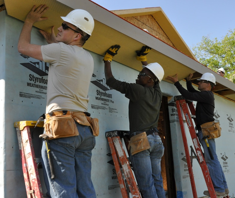 (left to right) Senior Airman Will Howell, 301st Aircraft Maintenance Squadron specialist, Chris, the future recipient of the house and Master Sergeant Gene Gaspar, 301st AMXS weapons expediter, are setting the panels to be nailed down.  Chris is originally from South Africa and has to contribute 250 volunteer hours in order to receive the house. These 301st AMXS members spent the day building a house for a local Fort Worth resident under the Habitat for Humanity program. (U.S. Air Force photo/Senior Airman Jeremy Roman)