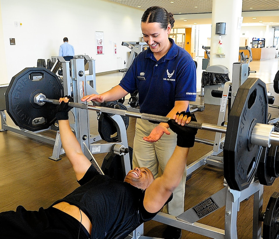 Senior Airman Danielle Galich, 436th Force Support Squadron sports program manager, spots Senior Airman Carnell Robinson, 736th Aircraft Maintenance Squadron crew chief, as he lifts weights April 30, 2013, at the Fitness Center on Dover Air Force Base, Del. She is ensuring that he is using the equipment correctly. (U.S. Air Force photo/Airman 1st Class Ashlin Federick)