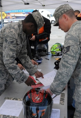 Participants sign waivers to participate in a motorcycle cruise on bikes provided on Motorcycle Safety Day April 26, 2013, Dover Air Force Base, Del. The 436th Airlift Wing Safety team put together the 8th Annual Motorcycle Safety Day to help combat the loss or life and limb for Dover AFB. (U.S. Air Force photo/Senior Airman Jared Duhon)