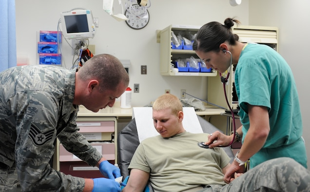 U.S. Air Force Staff Sgt. Andrew Day, 366th Medical Operations Squadron aerospace medicine technician and 1st Lt. Stephanie Doane, 366th MDOS clinical nurse, demonstrate proper care of a simulated patient, April 30, 2013, at Mountain Home Air Force Base, Idaho. MHAFB will celebrate Nurse and Medical Technician Appreciation Week May 6 through 12. (U.S. Air Force photo by Airman 1st Class Shane M. Phipps/Released)