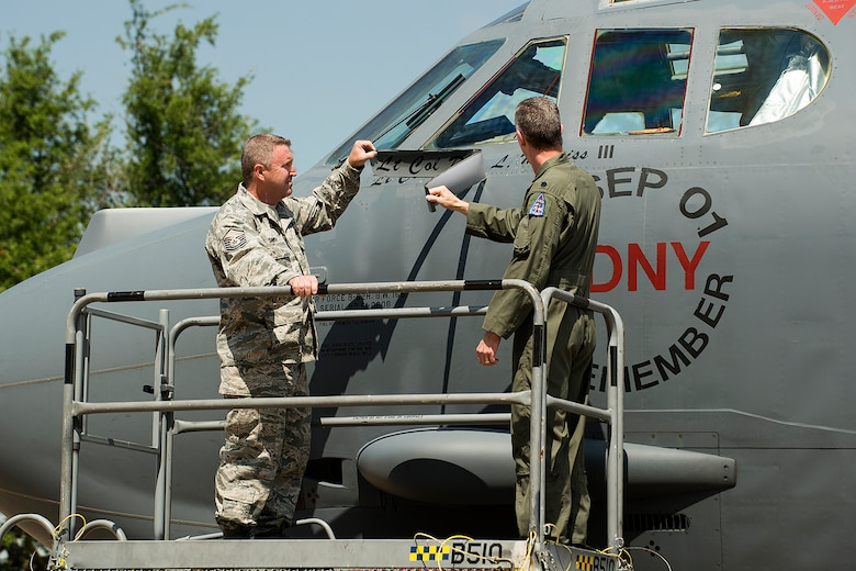 U.S. Air Force Lt. Col. Trey Morriss (right), 93rd Bomb Squadron (BS) commander, and U.S. Air Force Master Sgt. Brandon Smith, 307th Aircraft Maintenance Squadron crew chief, unveils the new commander's name on the side of a B-52H Stratofortress, April 28, 2013, Barksdale Air Force Base, La. Morriss assumed command of the 93rd BS and was previously the 307th Operations Group vice commander. (U.S. Air Force photo by Master Sgt. Greg Steele/Released)