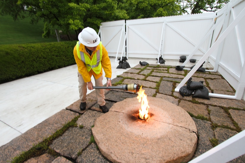 ARLINGTON, Va. – Randy Barton, an Arlington National Cemetery engineering technician, lights a torch from the John F. Kennedy Eternal Flame April 29, 2013. The torch was used to transfer the flame to a temporary burner while the permanent flame undergoes repair and upgrade work to install new burners, a new igniter as well as new gas and air lines. (U.S. Army photo/Patrick Bloodgood)