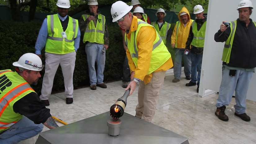 ARLINGTON, Va. – Randy Barton, an Arlington National Cemetery engineering technician, lights a temporary flame using a torch that was lit from the John F. Kennedy Eternal Flame at the cemetery April 29, 2013. The temporary flame will burn while the permanent flame undergoes repair and upgrade work to install new burners, a new igniter and new gas and air lines. Work on the burner itself will take about three weeks to complete. (U.S. Army photo/Patrick Bloodgood)