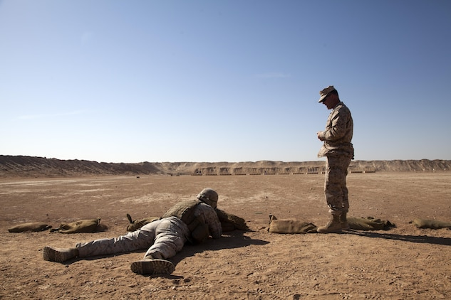 Chief Warrant Officer 4 Matthew Carpenter, right, the infantry weapons officer with Regimental Combat Team 7, coaches a Marine during a range here, Oct. 17, 2012. Carpenter, a native of Perry County, Penn., has deployed 12 times including five to Iraq and two to Afghanistan.