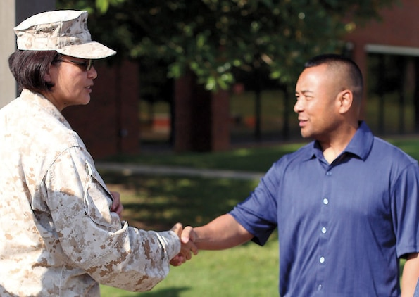 Master Gunnery Sgt. Paz T. Platt, left, of Marine Corps Logistics Command welcomes Maj. Jose M. Tee back with a handshake after his deployment to Afghanistan, July 25.