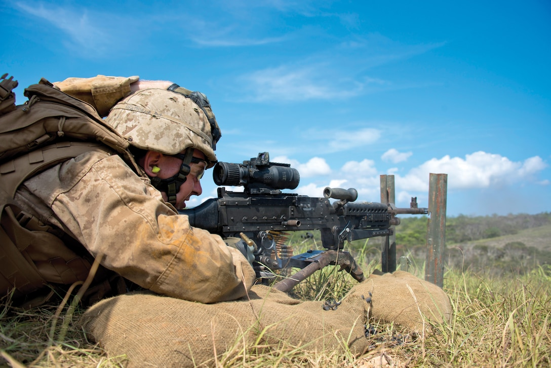 Pfc. Nathaniel A. Henthorne engages and suppresses targets July 22 at Range 10 near Camp Schwab during a combined-arms exercise. Marines with Combat Engineer Co., CAB, worked with mortarmen with 3rd Battalion, 6th Marine Regiment, to suppress targets with medium and light machine gun fire along with 60 mm mortars, allowing a squad of combat engineers to maneuver to and reduce obstacles. The engineers used bangalore torpedoes to clear a path through the danger area before confirming the passageway was clear and marked the lane for follow-on forces. Henthorne is a combat engineer with Combat Engineer Co., CAB, 3rd Marine Division, III MEF. 3rd Bn., 6th Marines, is assigned to 4th Marines, 3rd Marine Division, III MEF, under the unit deployment program. Photo by Cpl. Mark W. Stroud