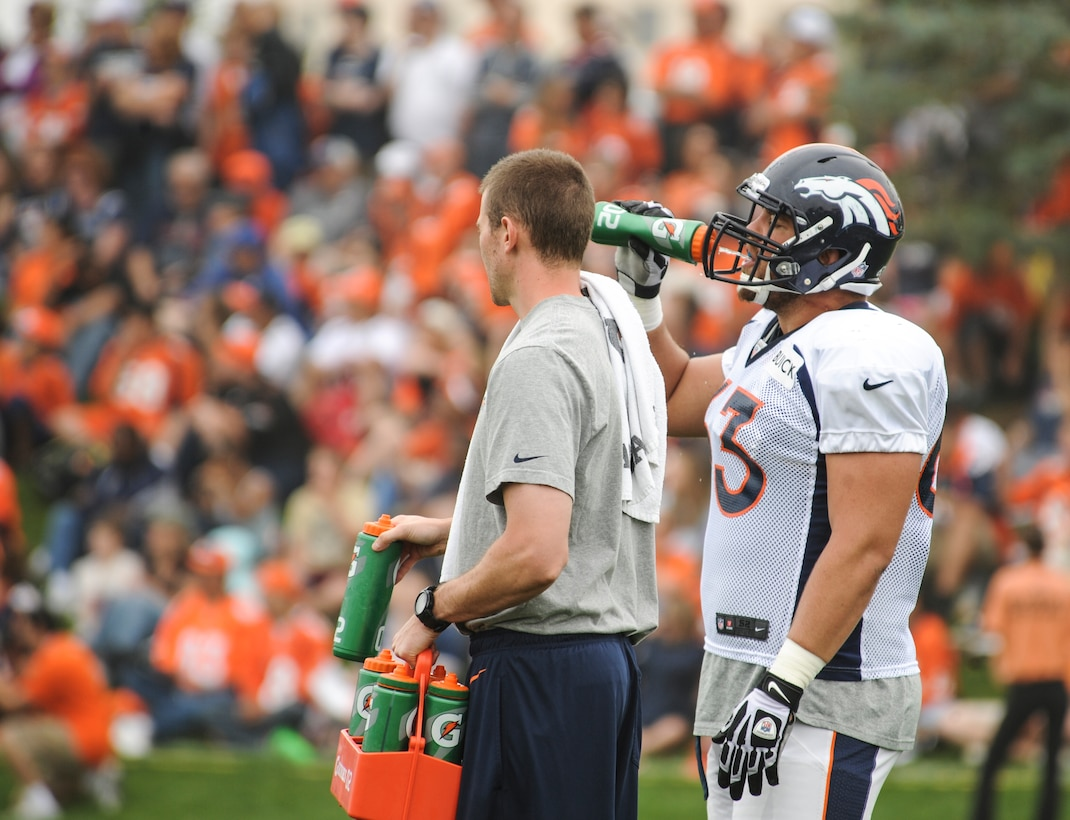 Benjamin Garland, Denver Broncos offensive guard, right, takes a water break during offensive line drills at a Broncos training camp practice July 29, 2013, at the Broncos training facility, Englewood, Colo. Garland spent last season on the Broncos practice squad and transitioned from defensive tackle to offensive guard before the Broncos 2013 mini-camp. Garland is also a first lieutenant for the 140th Wing, Colorado Air National Guard, and served his annual commitment during the early part of 2013. (U.S. Air Force photo by Staff Sgt. Christopher Gross/Released)